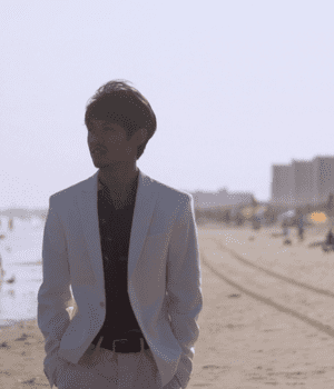 Man in a tanned suit at the beach. His jacket is open, with a dark, patterned shirt beneath. He looks back towards the tall buildings encircling the beach.