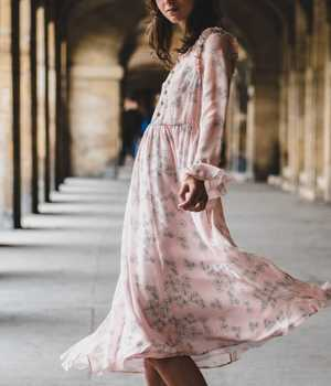 Model in long light-pink silk dress, with flower pattern, plenty of details, and an stylish finish.